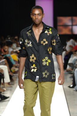 2008 - 2009 Runway Collection. Egungun flowers. He had a story he didn't care to tell. Black on black striped voile shirt African ancestral applique paired with khaki Other Pants.