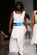 2008 - 2009 Runway Collection. Vest with pleated front and high and low neck line detail. with bealted hip band and applique belt. Skirt with inverted pleat and pocket detail.